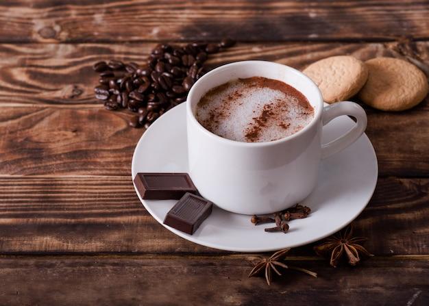 Berretto di caffè con schiuma, torte, chicchi di caffè a forma di cuore e cioccolato sul tavolo di legno