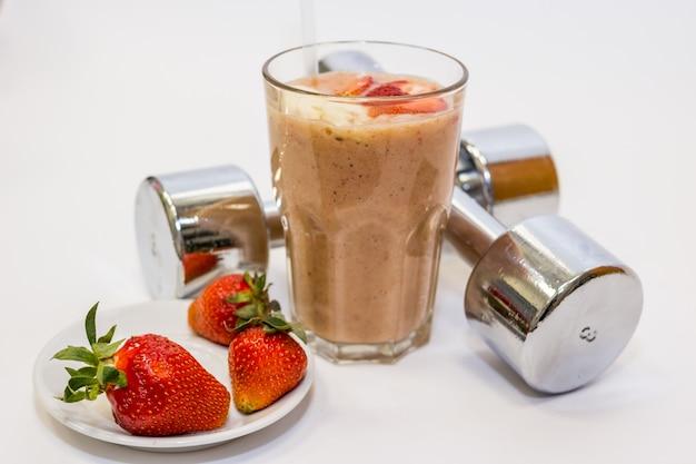 Berry fitness cocktail con avena, farina d'avena con menta. due manubri in metallo.