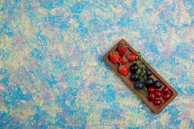 Berry mix su un piatto di legno isolato nell'angolo