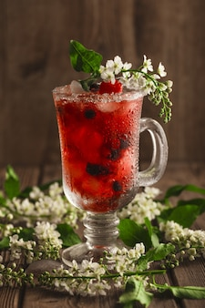 Berry soft drink con ghiaccio su una superficie di legno con fiori