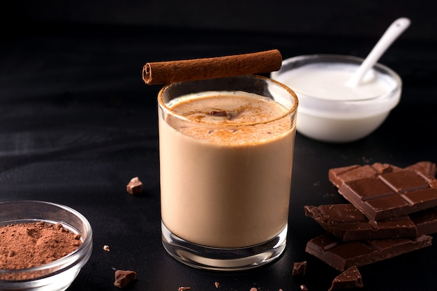 Bevanda al cioccolato indiano lassi su uno sfondo nero accanto agli ingredienti con yogurt, cacao e cioccolato