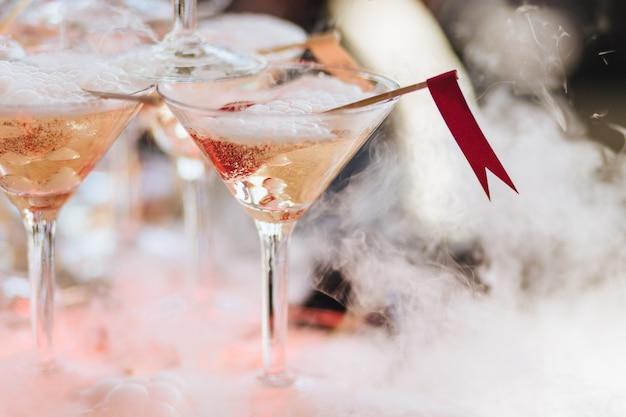 Bevanda alcolica o cocktail in vetro con ghiaccio e nebbia bianca.