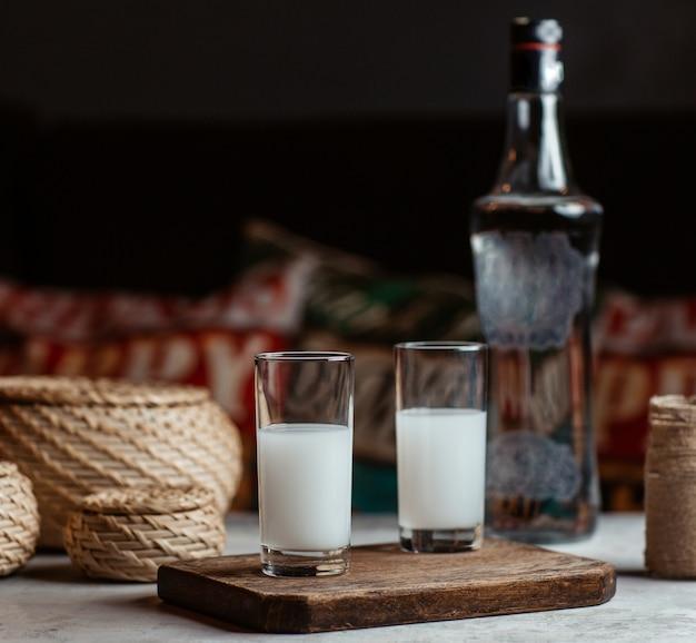 Bevanda alcolica turca raki, vodka, in due piccoli bicchieri.