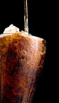 Bevanda analcolica che versa al vetro con i cubetti di ghiaccio tritati isolati su fondo scuro con lo spazio della copia. c'è una goccia d'acqua sulla superficie del vetro trasparente.