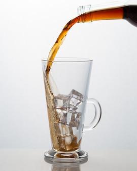 Bevanda analcolica che versa in una tazza di vetro