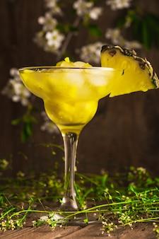 Bevanda analcolica di frutta ananas con ghiaccio su una superficie di legno con fiori