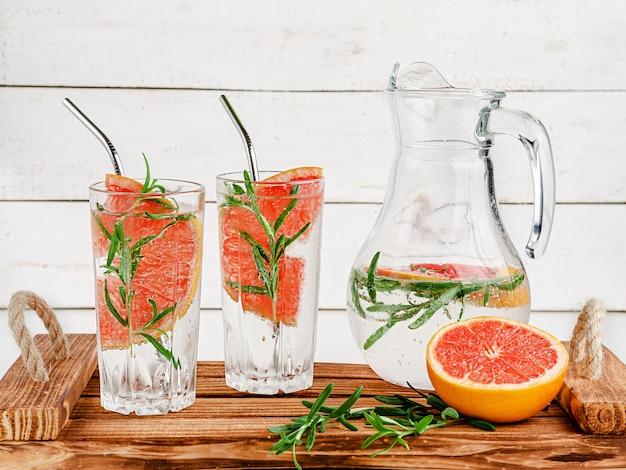 Bevanda antiossidante con soda, pompelmo e rosmarino su fondo di legno bianco. mangiare sano e bere il concetto.