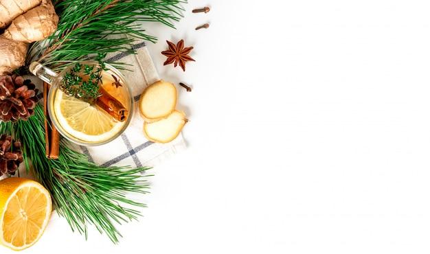 Bevanda aromatica invernale calda. tè allo zenzero con limone, cannella, anice stellato, coni e rami di albero di natale verde su sfondo bianco, vista dall'alto, disposizione piatta, spazio di copia.