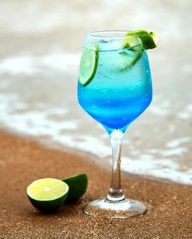 Bevanda blu con calce sulla riva del mare