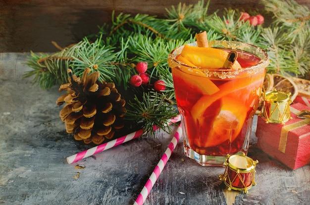 Bevanda calda al vin brulè con arancia e decorazioni natalizie