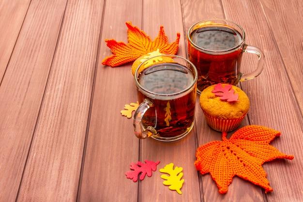 Bevanda calda d'autunno. tè nero con cupcakes, foglie colorate