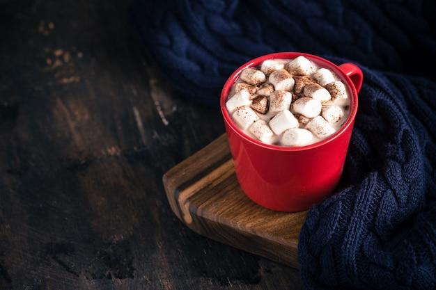 Bevanda calda invernale o autunnale, cioccolata calda o cacao, marshmallow e maglione lavorato a maglia
