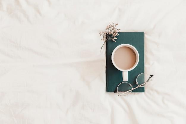 Bevanda calda, occhiali e erba sdraiata sul libro sul lenzuolo