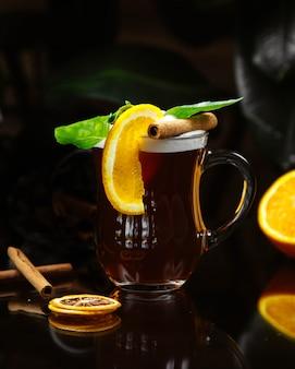 Bevanda condita con fetta d'arancia cannella e foglie