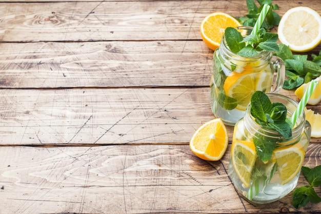 Bevanda della limonata delle foglie del selz, del limone e di menta in barattolo su fondo di legno.