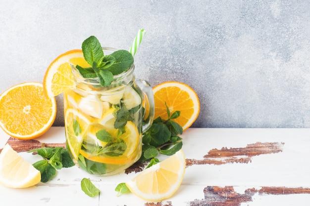 Bevanda della limonata delle foglie del selz, del limone e di menta in barattolo su fondo leggero.