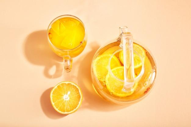 Bevanda della vitamina in un bollitore di vetro con l'arancia e l'olivello spinoso su giallo