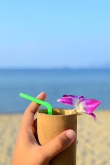 Bevanda di benvenuto con vetro di bambù e decorare con orchidea viola su sabbia, mare e cielo blu sullo sfondo.