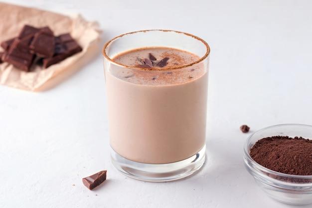 Bevanda di cioccolato indiano lassi accanto a cioccolato e cacao su uno sfondo bianco