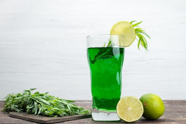 Bevanda di dragoncello fresco vista frontale all'interno di vetro lungo con limoni e foglie di dragoncello fresco su bianco, succo di dragoncello verde bevanda