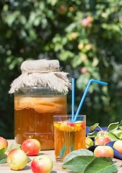 Bevanda di kombucha in un barattolo di vetro e un bicchiere con due cannucce, mele fermentate, su un tavolo di legno. stile rustico.