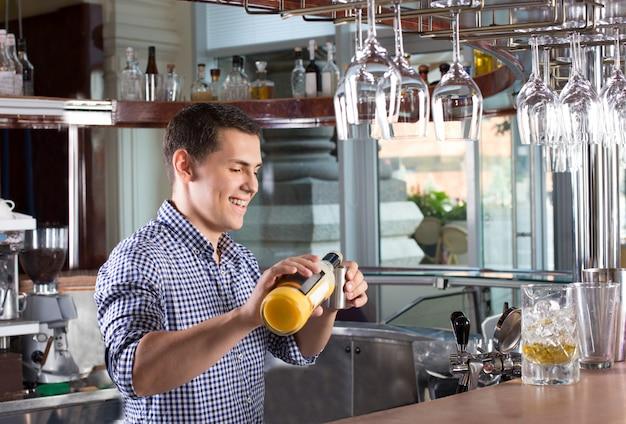 Bevanda di versamento sorridente felice del barista in un jigger d'acciaio.