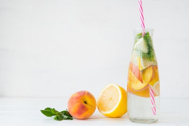 Bevanda disintossicante fatta in casa di limone e pesca in una bottiglia.