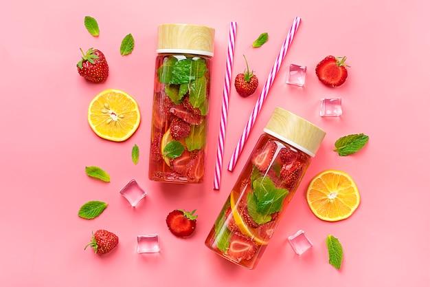 Bevanda estiva con fragole, limone, foglia di menta su sfondo rosa.