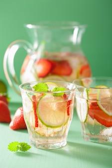 Bevanda estiva rinfrescante con lime cetriolo fragola in barattolo e bicchieri