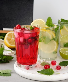 Bevanda estiva rinfrescante di fragole e mirtilli rossi su una tavola di legno bianca