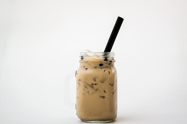 Bevanda fredda della bolla del tè e della bibita del latte del ghiaccio di vetro su fondo bianco