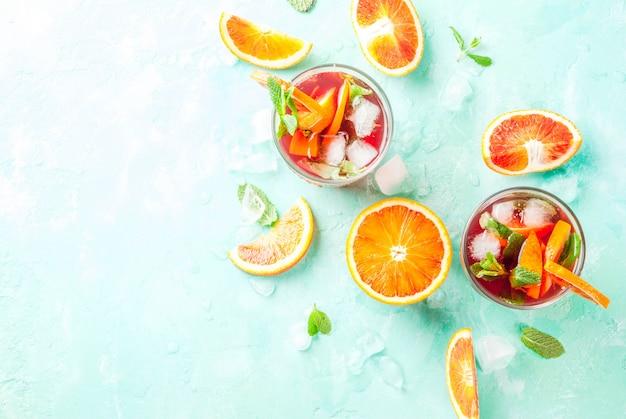 Bevanda fredda di estate, mimosa del cocktail della menta dell'arancia sanguinella, mojito o sangria, blu-chiaro, vista superiore del copyspace