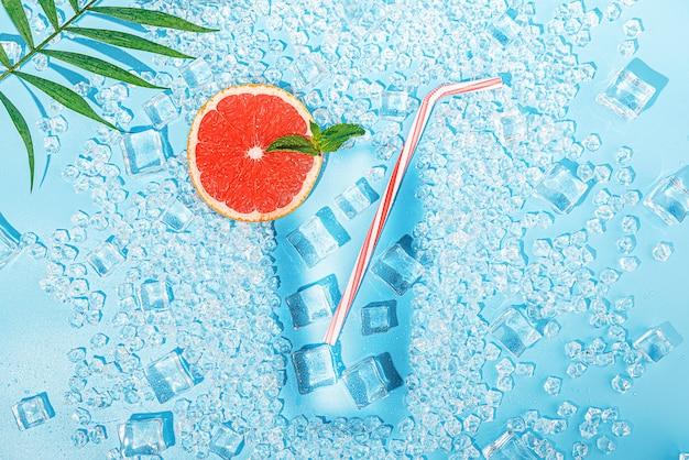 Bevanda fredda. ghiaccio su uno sfondo blu chiaro presentato sotto forma di un bicchiere con un tubulo per un cocktail e una fetta di pompelmo