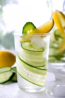 Bevanda fresca con erbe di cetriolo, limone e rosmarino. limonata estiva fredda. sul muro bianco
