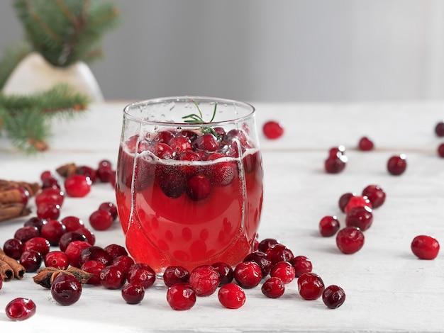 Bevanda fresca del mirtillo rosso in una tazza di vetro. mirtilli e spezie sul tavolo.