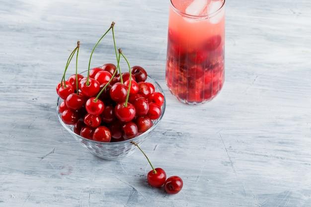 Bevanda ghiacciata della ciliegia in una brocca con le ciliege alte