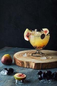 Bevanda giallo arancione con i fichi e l'uva su un supporto di legno