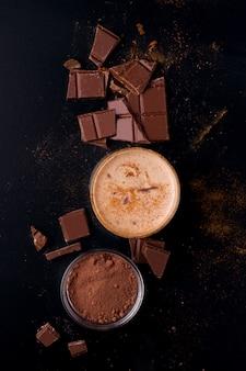 Bevanda indiana del cioccolato di lassi su un fondo nero accanto a cacao su una vista superiore del fondo nero