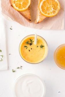 Bevanda indiana del mango di lassi accanto a yogurt e ai panini su calcestruzzo bianco