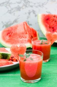 Bevanda mescolata anguria fresca con foglie di menta e un cuore di anguria in bicchieri su un tavolo di legno