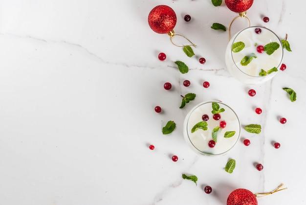 Bevanda rinfrescante autunno e inverno bere mojito di natale bianco cocktail con mirtillo rosso e menta sul tavolo bianco