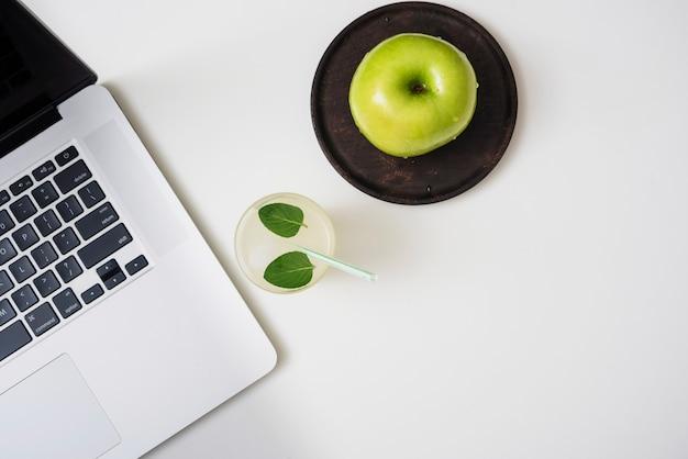 Bevanda rinfrescante con mele e laptop
