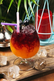 Bevanda rinfrescante dell'uva rossa in vetro con i cubetti di ghiaccio