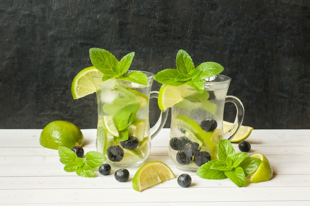 Bevanda rinfrescante di estate limonata o cocktail mojito con lime e menta fresca mirtillo ghiaccio.