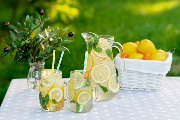 Bevanda rinfrescante di limonata in una brocca e vasetti con limoni, menta fresca e ghiaccio con un cesto di limoni e kumquat su un tavolo da giardino. picnic estivo all'aperto. messa a fuoco selettiva morbida.