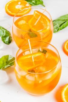 Bevanda rinfrescante estiva cocktail di limonata con arancia e basilico su un tavolo di marmo bianco
