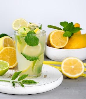 Bevanda rinfrescante estiva limonata con limoni, foglie di menta, lime in un bicchiere