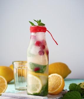 Bevanda rinfrescante estiva limonata con limoni, mirtilli rossi, foglie di menta, lime in una bottiglia di vetro