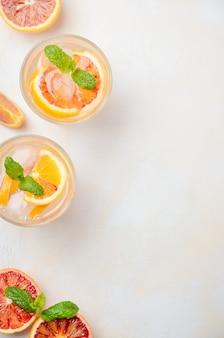 Bevanda rinfrescante fredda con fette di arancia rossa in un bicchiere. vista dall'alto, disteso, copia spazio.