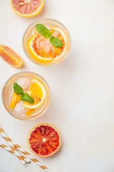 Bevanda rinfrescante fredda con le fette dell'arancia sanguinella in un vetro su una tavola di calcestruzzo bianca
